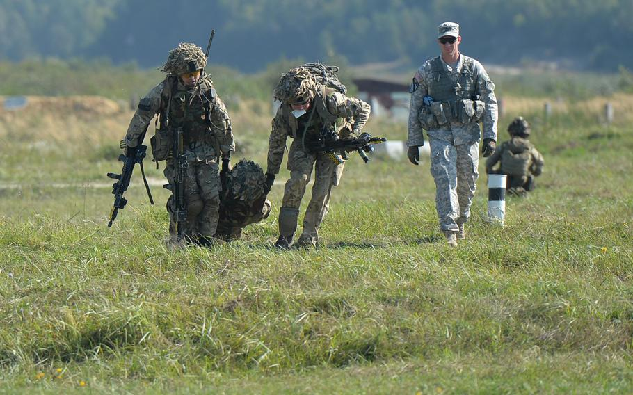 """British soldiers carry a """"wounded"""" comrade during training at Exercise Rapid Trident near Yavoriv, Ukraine, Thursday, Sept. 18, 2014, as Sgt. 1st Class Josh Ward of the Joint Multinational Readiness Center watches."""