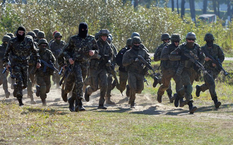 Soldiers from various nations hustle back to the starting point after taking part in cordon-and-search training at Exercise Rapid Trident near Yavoriv, Ukraine, Friday, Sept. 19, 2014.