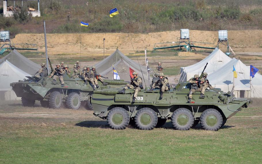 Ukrainian soldiers ride on an armored personnel carrier during a mock attack on a forward operating base at Exercise Rapid Trident near Yavoriv, Ukraine, Friday, Sept. 19, 2014. Friday was media and VIP day at the exercise. Among the dignitaries watching the action were Secretary of the Army John McHugh, USAREUR commander Lt. Gen. Donald Campbell and Lt. Gen. Ben Hodges, commander NATO Allied Land Command.