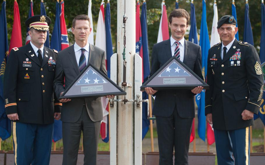 U.S. Army Garrison Ansbach commander Col. Christopher Benson and Command Sgt. Maj. Mark Kiefer flank the Schweinfurt Lord Mayor Sebastian Remelé and the Schweinfurt county commissioner, Florian Topper, each holding one of the final American flags to be flown over the Schweinfurt military base, Sept. 19, 2014.