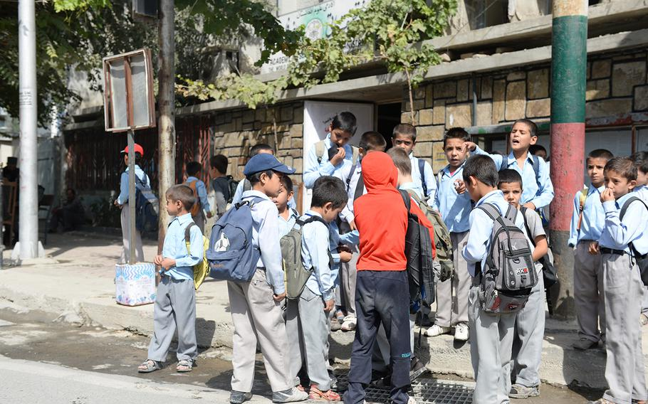 Afghan school children gather around the site of a magnetic bomb attack that injured the driver of an Afghan military vehicle outside the presidential palace in Kabul, on Sunday, Sept. 28, 2014. The blast sparked concerns that insurgents would try to disrupt Monday's swearing-in ceremony for Ashraf Ghani, Afghanistan's new president.