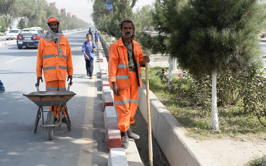 Street cleaning crews dot Airport Road in Kabul on Sunday, Sept. 28, 2014, a day ahead of presidential inauguration ceremony.
