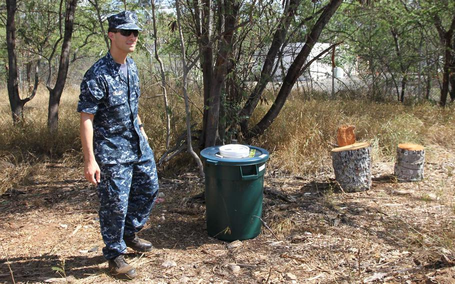 Lt. j.g. Eric Galassi on Wednesday stands beside one of the barrel-style beetle monitors deployed throughout Joint Base Pearl Harbor-Hickam, which are baited with pheremones, UV lights and rotting palm wood. Earlier in the morning Galassi had discovered a beetle lying on its back atop the monitor, unable to right itself.