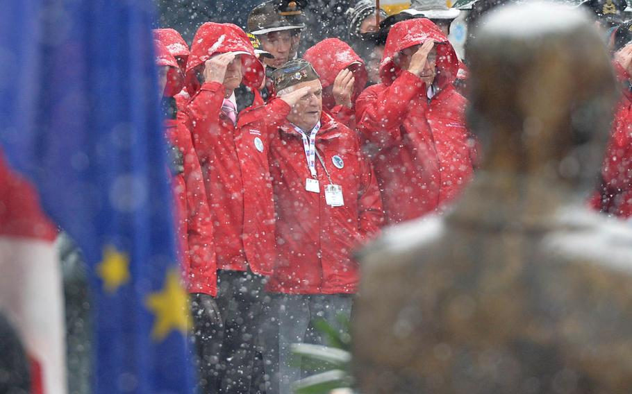 American World War II veterans salute during a wreath-laying ceremony on McAuliffe square in Bastogne, Belgium, Saturday, Dec. 13, 2014. The ceremony was part of commemorations marking the 70th anniversary of the Battle of the Bulge. The statue of Gen. Anthony McAuliffe is in the foreground at right.