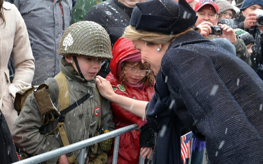 Queen Mathilde of Belgium talks to a boy wearing World War II-style garb following a wreath-laying ceremony in Bastogne, Belgium, Dec. 13, 2014, that was part of commemorations marking the 70th anniversary of the Battle of the Bulge.