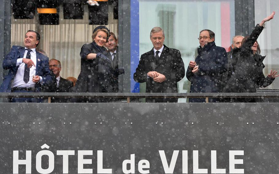 """The mayor of Bastogne Benoit Lutgen, left, Queen Mathilde and King Philippe of Belgium, Thomas Nides, the head of the U.S. presidential delegation, and Denise Campbell Bauer, the U.S. Ambassador to Belgium, throw nuts from the city hall balcony as part of the 70th anniversary commemorations of the Battle of the Bulge in Bastogne, Belgium, Saturday, Dec. 13, 2014. Responding to the Germans' request for the Americans to surrender, Brig Gen Anthony McAuliffe famously replied with a single word: """"Nuts,"""" which an officer explained to the Germans meant they could go to hell."""