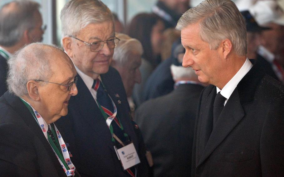 King Philippe of Belgium, right, talks to World War II veteran Carl Wiggs, left, as fellow vet Robert Thompson, center, listens at a reception during commemorations of the 70th anniversary of the Battle of the Bulge in Bastogne, Belgium, Saturday, Dec. 13, 2014.