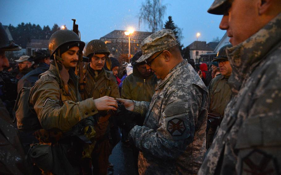 American soldiers and World War II re-enactors discuss equipment before the start of the annual commemorative walk in Bastogne, Belgium, Dec. 14, 2014. The march was one of the events marking the 70th anniversary of the Battle of the Bulge.