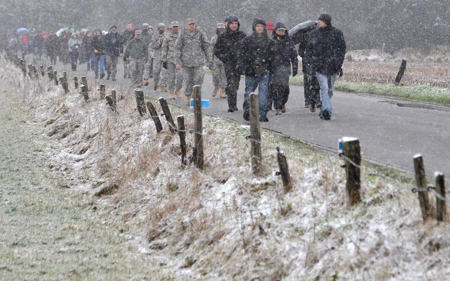 Participants in the annual commemorative march in Bastogne, Belgium, walk through the snow along a road on the outskirts of the city, Saturday, Dec. 13, 2014. The march was one of the events marking the 70th anniversary of the Battle of the Bulge.