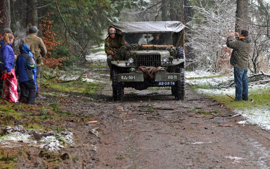 People taking part in the annual commemorative march in Bastogne, Belgium, watch a World War II-era vehicle driven by re-enactors pass along a muddy road outside of town, Saturday, Dec. 13, 2014. The march was one of the events marking the 70th anniversary of the Battle of the Bulge.