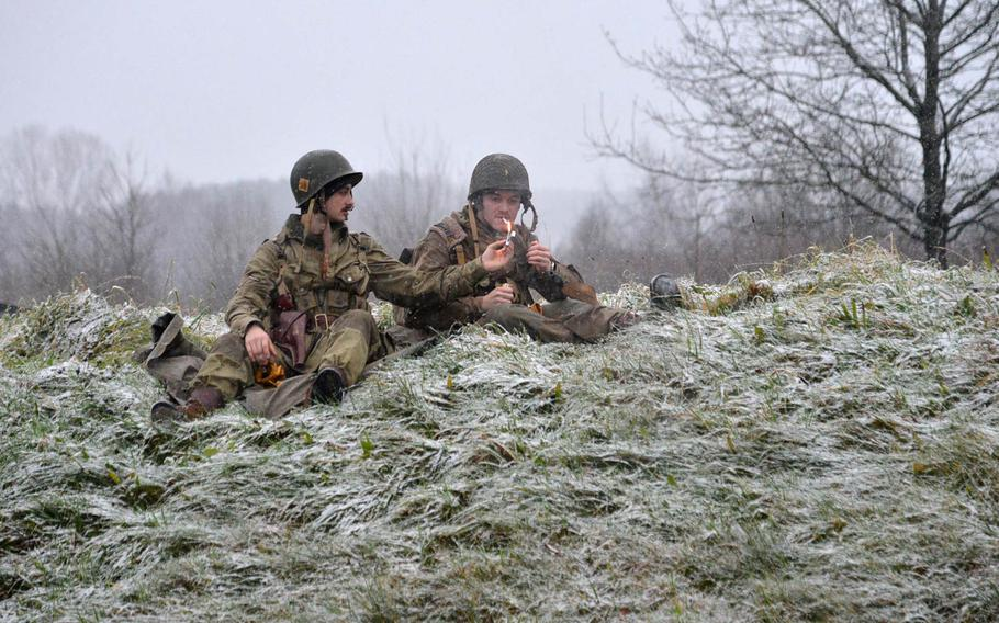 World War II re-enactors sit in a snowy field outside Bastogne, Belgium, Saturday, Dec. 13, 2014. Scores of re-enactors were in town as it marked the 70th anniversary of the Battle of the Bulge.