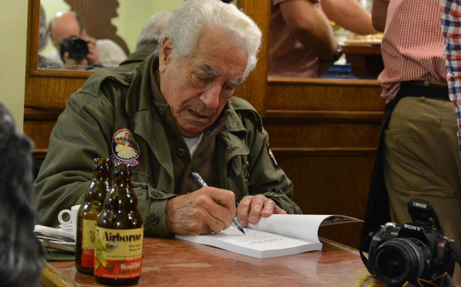 Battle of the Bulge veteran Vincent Speranza autographs a book in Le Nut's Cafe in Bastogne, Belgium, Friday, Dec. 12, 2014. The 501st Infantry Regiment vet was in town for the commemorations marking the 70th anniversary of the battle.