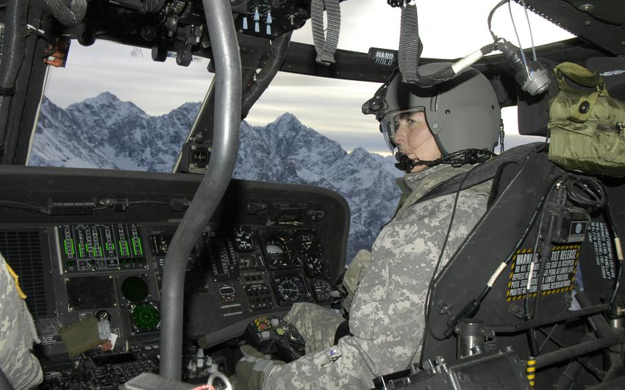Alaska Army National Guard Chief Warrant Officer 4 Pamela Vitt guides a UH-60 Black Hawk helicopter over mountains near Anchorage on Feb. 13, 2015. Pilots and other crewmembers take part in cold-weather survival training in case they are forced to make an emergency landing in the Alaska wilderness.