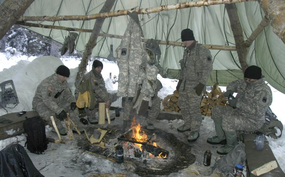 Army aviators stay warm during Arctic survival training in Alaska on Feb. 10, 2015. The soldiers huddled together for warmth around a large, comforting blaze under a parachute that kept snow flurries from their heads.   Seth Robson/Stars and Stripes