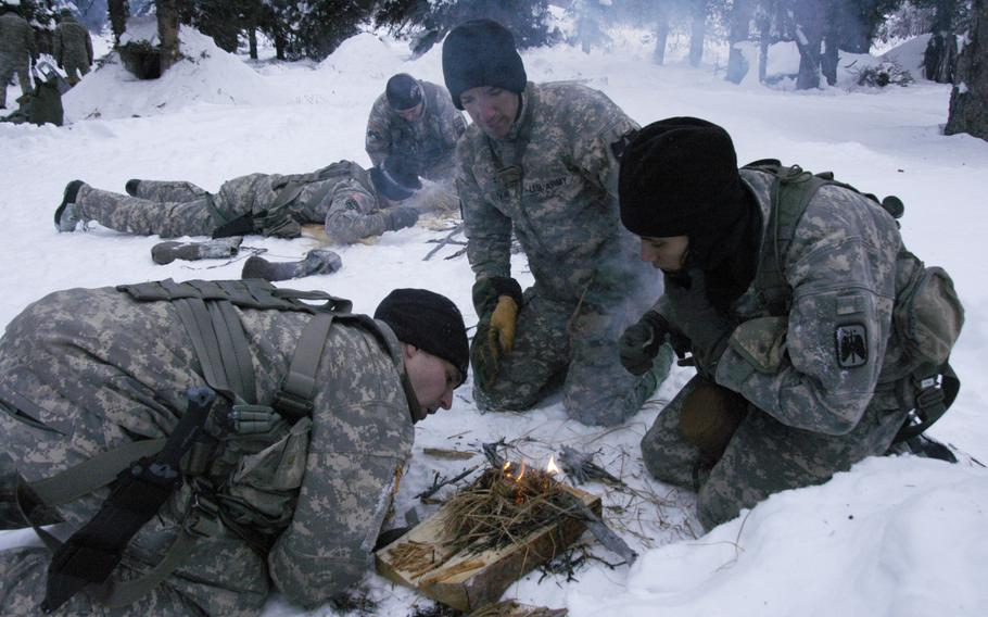 Army aviators make fires from dry grass during arctic survival training at the Northern Warfare Training Center in Alaska on Feb. 10, 2015.