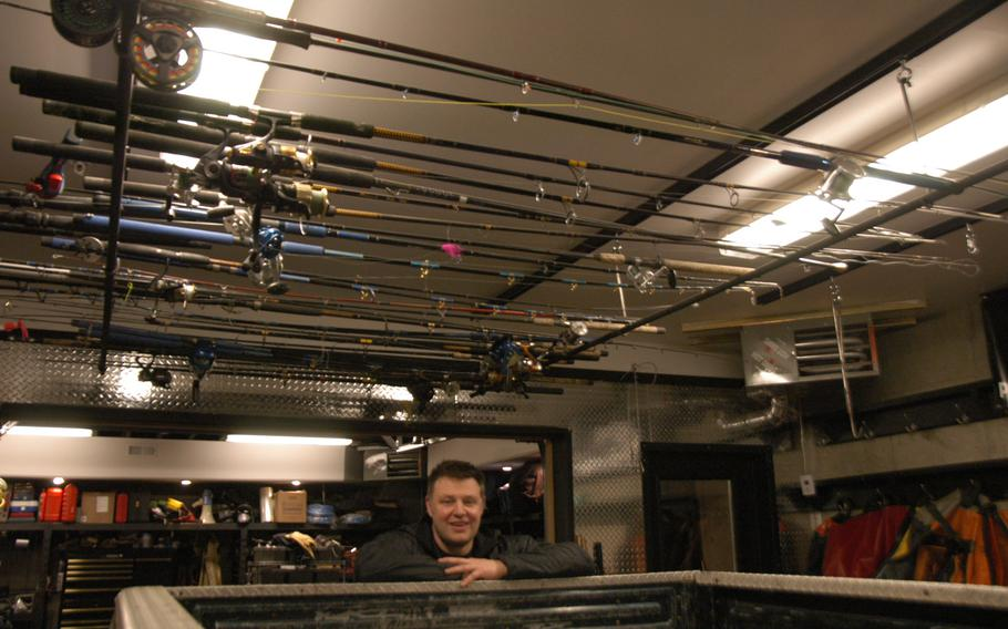 Anchorage businessman Justin Green hangs his fishing rods from the ceiling of his garage. Fishing is one of the most popular sports in the 49th state.