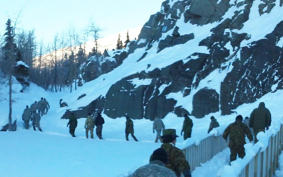 U.S. and foreign troops hike past rock outcrops used to teach military mountaineering at the Black Rapid Training Site, Alaska, in February 2015.