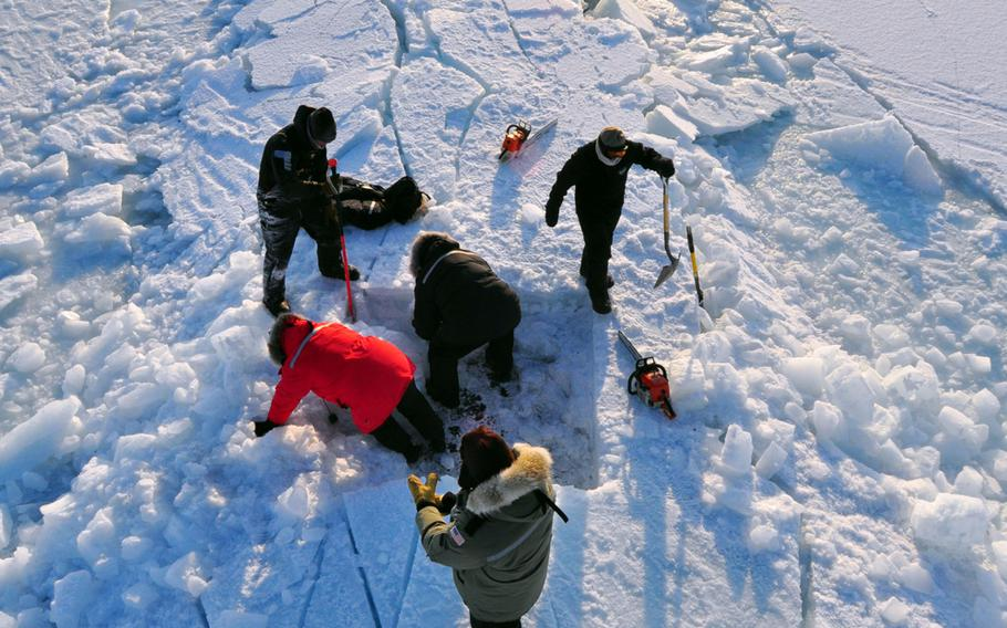 Members of the Applied Physics Laboratory Ice Station clear ice from the hatch of the Los Angeles-class submarine USS Annapolis after the sub broke through the ice while participating in Ice Exercise 2009 in the Arctic Ocean. The crews of the Annapolis and the Los Angeles-class attack submarine USS Helena were learning to operate in the challenging and unique environment that characterizes the Arctic region.