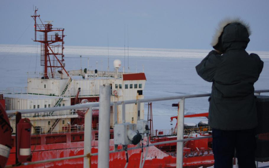 A Coast Guard Cutter Healy crewmember takes a moment to watch the Russian-flagged tanker Renda steam through the ice in the North Bering Sea while the cutter crew escorts the tanker to Nome on Jan. 6, 2012.