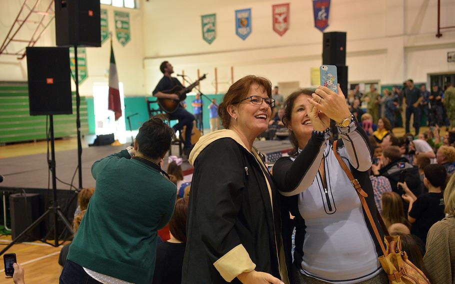 """Audience members take selfies as former American Idol contestant Phillip Phillips performs at the USO Spring Troop visit in Naples, Italy, on Monday, March 3, 2015. Phillips is one of 10 celebrities joining Vice Chairman of the Joint Chiefs of Staff Adm. James """"Sandy"""" Winnefeld on the tour, which was to visit overseas military bases over seven days."""