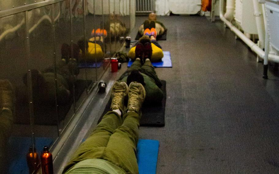 Marines and sailors conduct an evening workout session in a passageway aboard the amphibious transport dock ship USS New York, Feb 28, 2015.