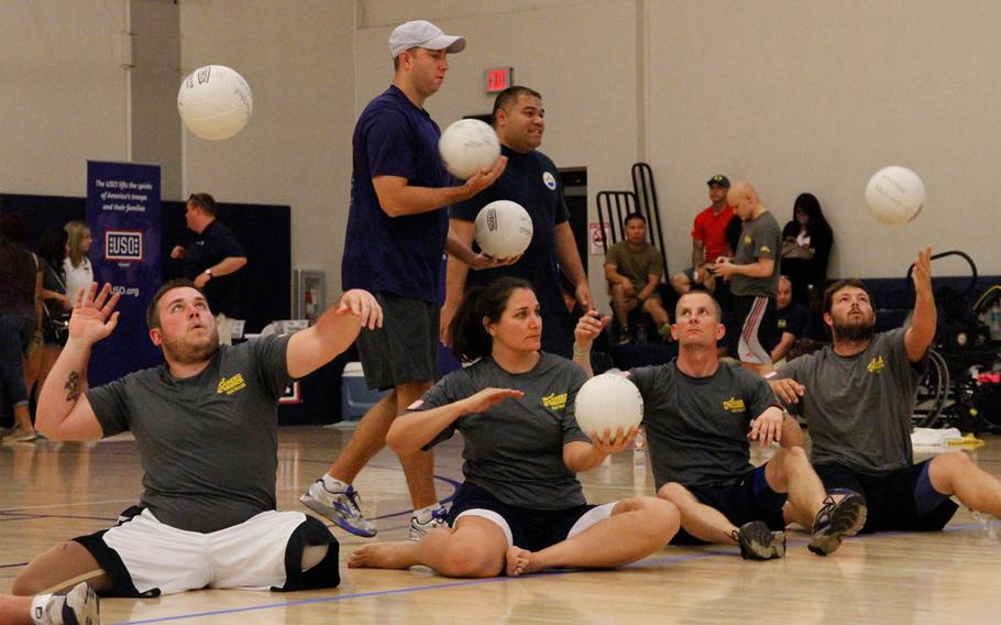 Athletes demonstrate their serving skill while sitting during the 1st day of trials at Joint Base Pearl Harbor-Hickam, Hawaii, for the Warrior Games to be held in June 2015. 'Seated' volleyball equalizes the playing ground for athletes with missing or injured legs.