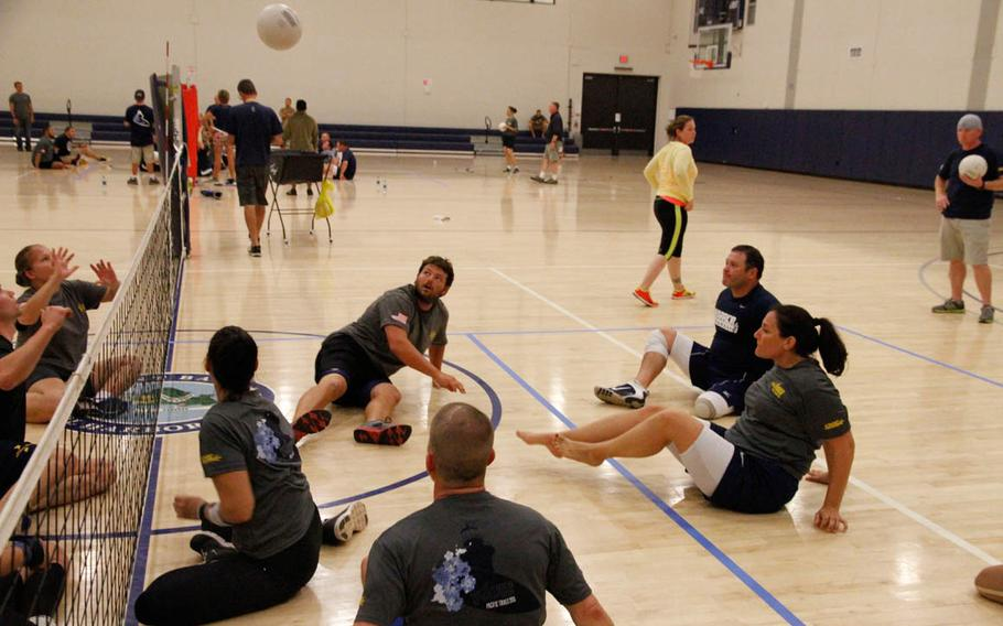 Athletes practice 'seated' volleyball at Joint Base Pearl Harbor-Hickam, Hawaii, during team trials by Navy Wounded Warrior-Safe Harbor for the multi-service Warrior Games competition to be held June 19-30, 2015.