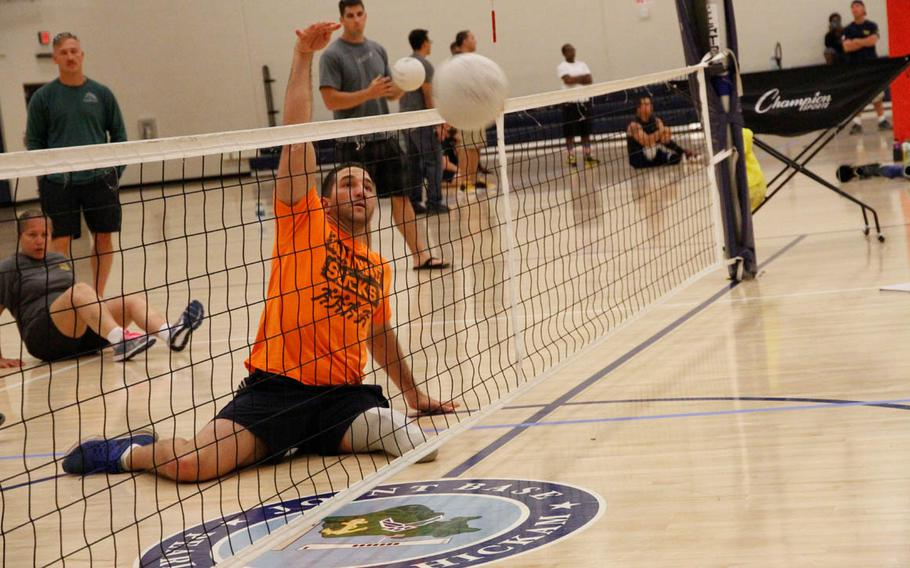 Redmond Ramos, a former Navy corpsman attached with the Marines, spikes a ball over the net during try-outs for 'seated' volleyball at the gym at Joint Base Pearl Harbor-Hickam, Hawaii, on Monday, March 9, 2015. Selected athletes will compete in June at the Warrior Games.