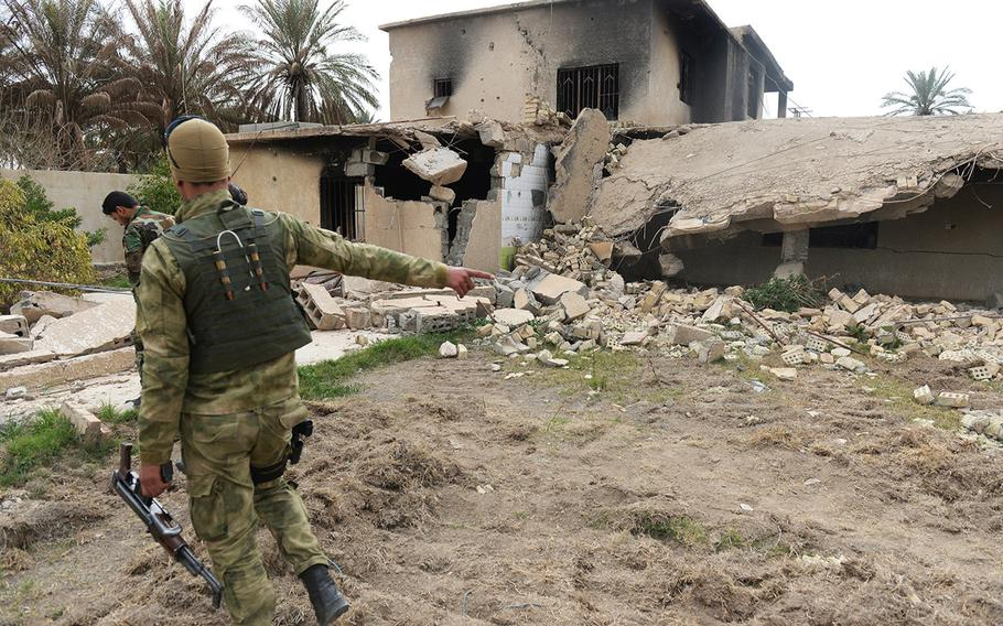 The purported former residence of an Islamic State commander lies in ruin in Jurf al-Nasr, Iraq, March 8, 2015. Government-backed militia patrolling the town say the building, like many others, was rigged to blow up before the militants were pushed out in October 2014.