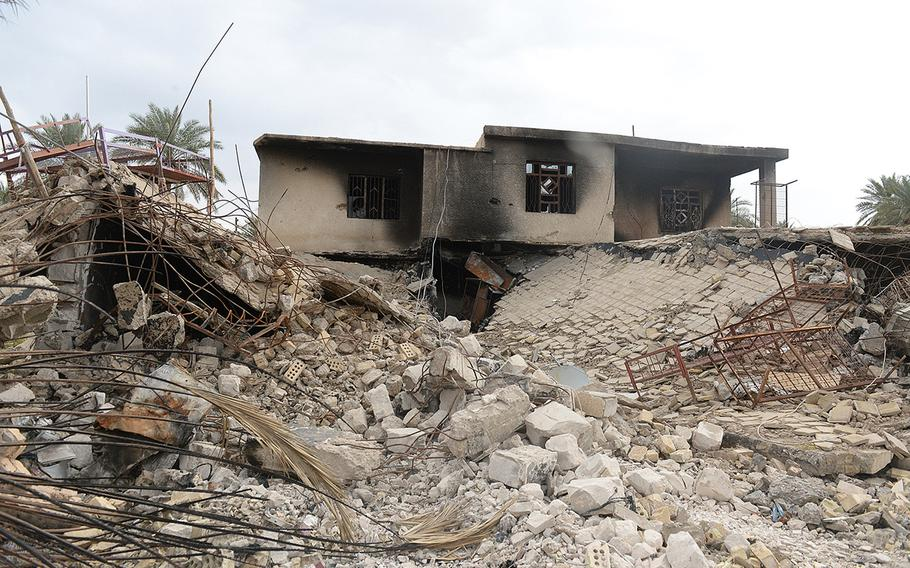 A building allegedly used by an Islamic State commander as a residence lies in ruin in Jurf al-Nasr, Iraq, March 8, 2015. This, like many other buildings in the town, was rigged to blow up before the militants were pushed out in October 2014.