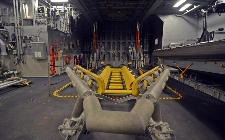 A rigid-hulled inflatable boat carried by the USS Fort Worth is lifted by a crane, loaded into this bay and then exits the craft through the doors ahead during missions, ship officials said during a tour in Busan, South Korea on Saturday.