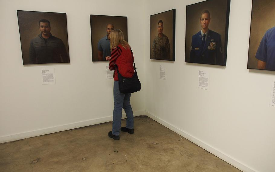"""A woman looks at the """"100 Faces of War Experience"""" at the National Veterans Art Museum in Chicago. The museum, founded by Vietnam veterans, is increasingly getting art from troops who served in Iraq and Afghanistan."""