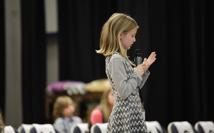 Ava Collins, representing Landstuhl Elementary-Middle School writes out a word on her hand before giving her answer Saturday, March 21, 2015, at the European PTA Spelling Bee at Ramstein Elementary School in Germany.