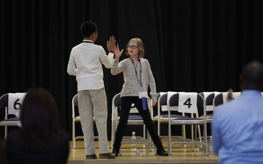 Grafenwohr Elementary School fourth-grader Ella Scheuermann and Naples sixth-grader Ryan Rayos high-five after Rayos properly spelled ''peloton'' to win the European PTA Spelling Bee Saturday, March 21, 2015, at at Ramstein Elementary School in Germany.