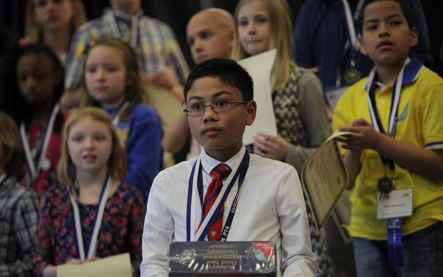 Naples sixth-grader Ryan Rayos holds a dictionary after winning the European PTA Spelling Bee Saturday, March 21, 2015, at at Ramstein Elementary School in Germany.