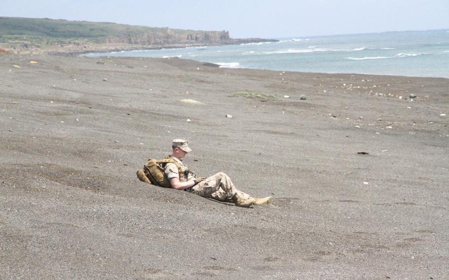 Navy corpsman Petty Officer 3rd Class Michael Vallet sits in the black Iwo Jima sands for a moment of solemn reflection during the 70th anniversary ceremony of the Battle of Iwo Jima on March 21, 2015.
