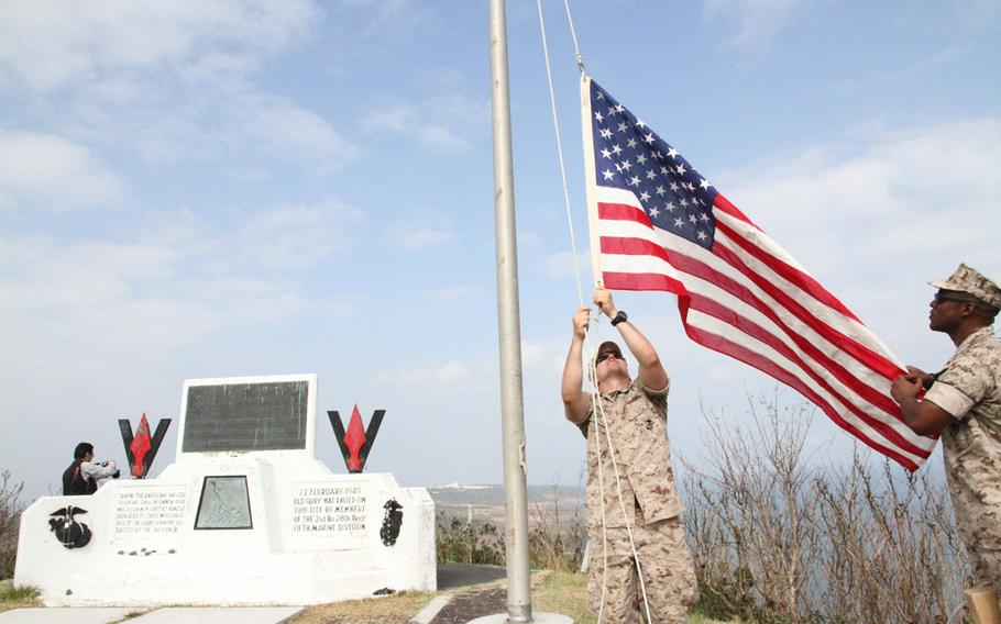 Marine 1st Lt. John Roberts, left, and Gunnery Sgt. Stephen Traynham raise a flag on Mount Suribachi near the spot of the iconic Iwo Jima flag raising following the ceremony marking 70 years since the battle.