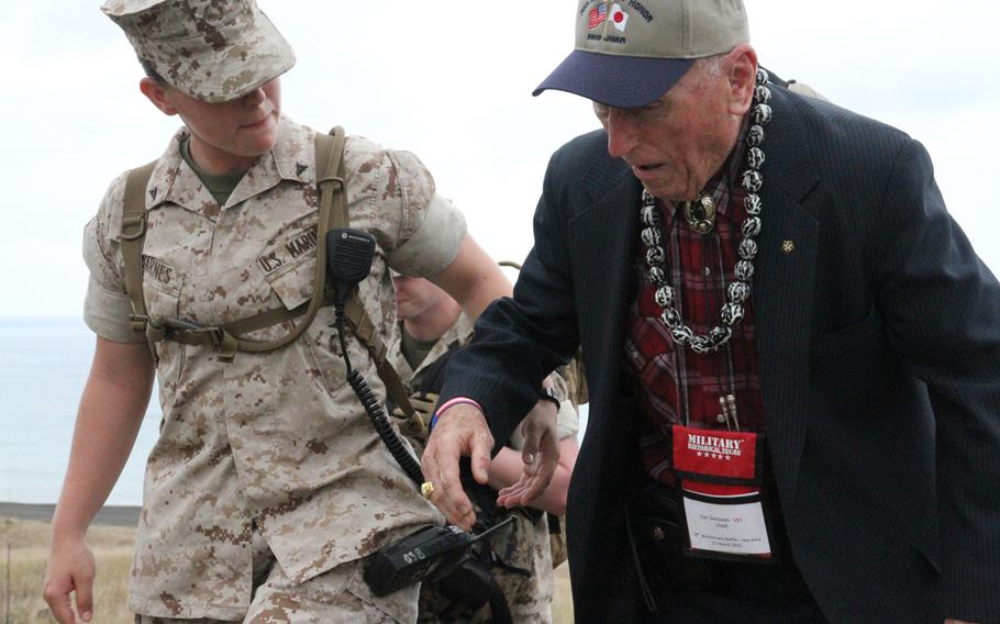Marine Lance Cpl. Morgan Barnes helps steady Battle of Iwo Jima veteran and fellow Marine Carl DeHaven as he makes his way to the ceremony commemorating the 70th anniversary of the World War II battle.