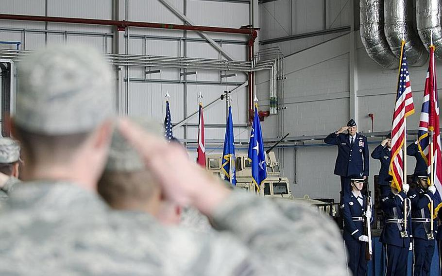 Lt. Gen. Bradley A. Heithold, commander of Air Force Special Operations, members of the audience salute during the opening of an activation ceremony at RAF Mildenhall, England, on Monday, March 23, 2015. The ceremony marked the deactivation of the 352nd Special Operations Group and its subsequent reactivation as a wing.  Adam L. Mathis/Stars and Stripes