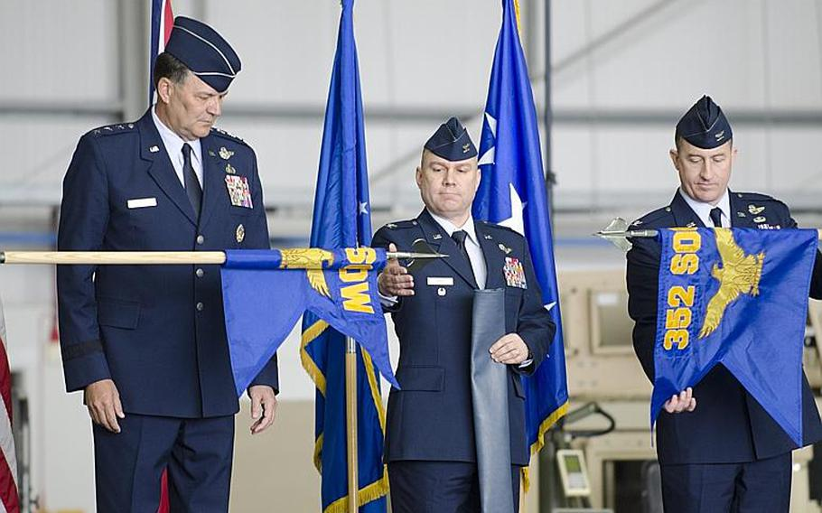 Lt. Gen. Bradley A. Heithold, commander of Air Force Special Operations, left, and Col. William G. Holt II, center, oversee the unfurlling of the 352nd Special Operations Wing flag, while Col. Nathan C. Green retires the 352nd Special Operations Group flag at RAF Mildenhall, England, on Monday, March 23, 2015. The 352nd has grown in the past few years from about 600 to about 1,200 airmen.   Adam L. Mathis/Stars and Stripes