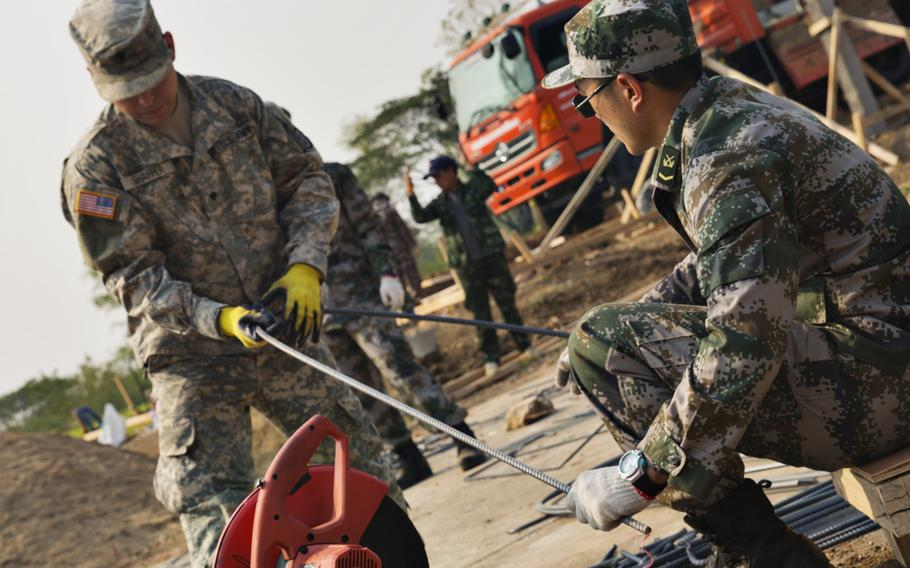 A U.S. Army soldier taking part in Cobra Gold 2015 hands a steel rod to a Chinese soldier during construction of a school in Chai Badan District, Thailand, on Jan. 24, 2015. A 2014 military coup in Thailand has splintered relations with the U.S., and some experts say that China is more than willing to step in and fill the void.