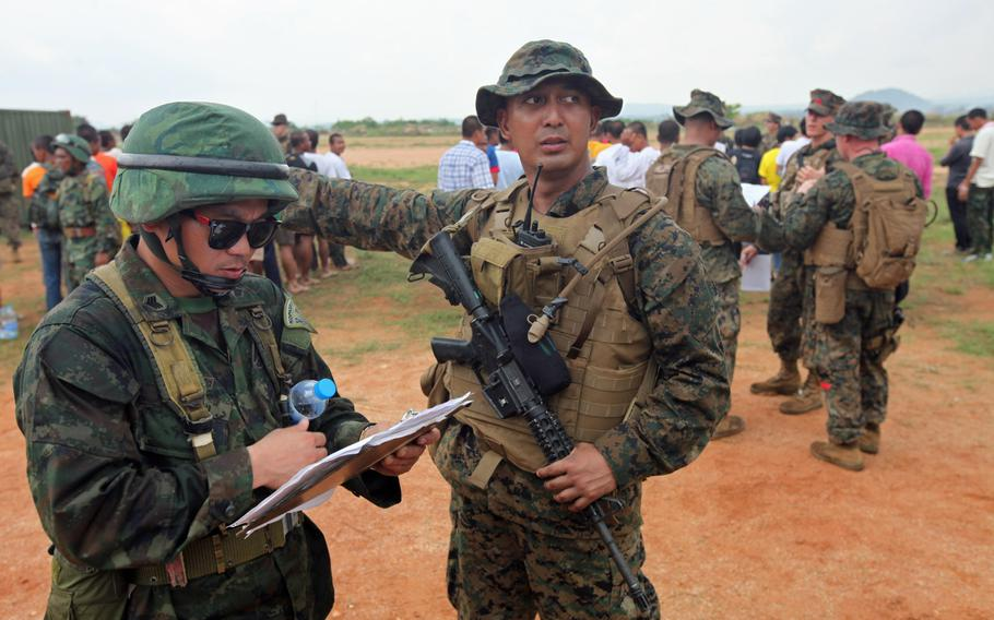 Gunnery Sgt. Marklester M. Ecalnir of 31st Marine Expeditionary Unit helps direct Thai citizens for a multinational noncombatant evacuation operation as part of Cobra Gold 2013 in Thailand.
