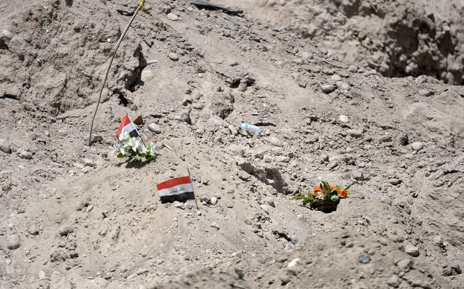 Flags and flowers mark the location of one of 13 mass graves found around Tikrit, Iraq. Islamic State militants massacred an estimated 1,700 people before burying or throwing their bodies in a river.