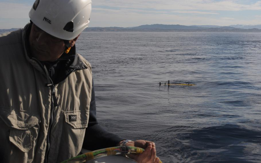 A crew member of the NATO research vessel NRV Alliance feeds a hydrophone cable into the water during the deployment of an autonomous underwater vehicle (pictured in the water). The hydrophone is a listening device that trails behind the AUV to pick up echoes from sound waves projected into the water by the Alliance. The ship and its detachment of scientists from NATO's Centre for Maritime Research and Experimentation in Italy are testing several AUVs in the North Sea off the coast of Norway as part of an anti-submarine warfare exercise called Dynamic Mongoose.