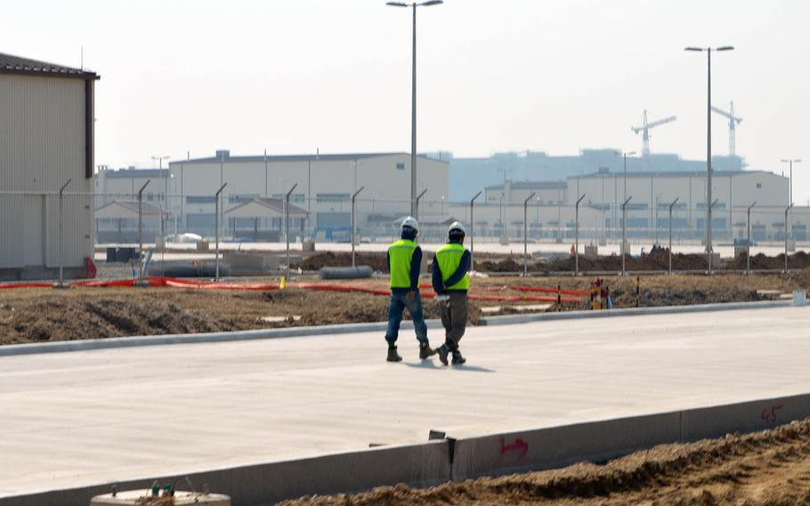 South Korean construction workers walk down an unfinished road at Camp Humphreys, South Korea, on April 24, 2015. The buildings behind the fence line are part of a new motor pool complex.