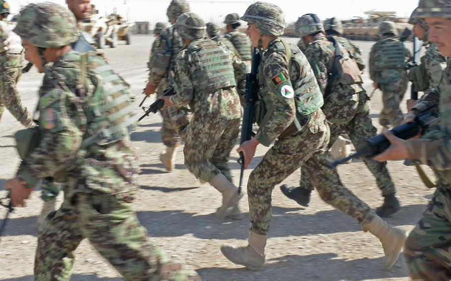Afghan soldiers with the army's 215 Corps sprint to their Humvees and armored personnel carriers ahead of a patrol May 12, 2015 at Camp Shorabak in Helmand province. This is the first fighting season for the soldiers without coalition forces in the province.