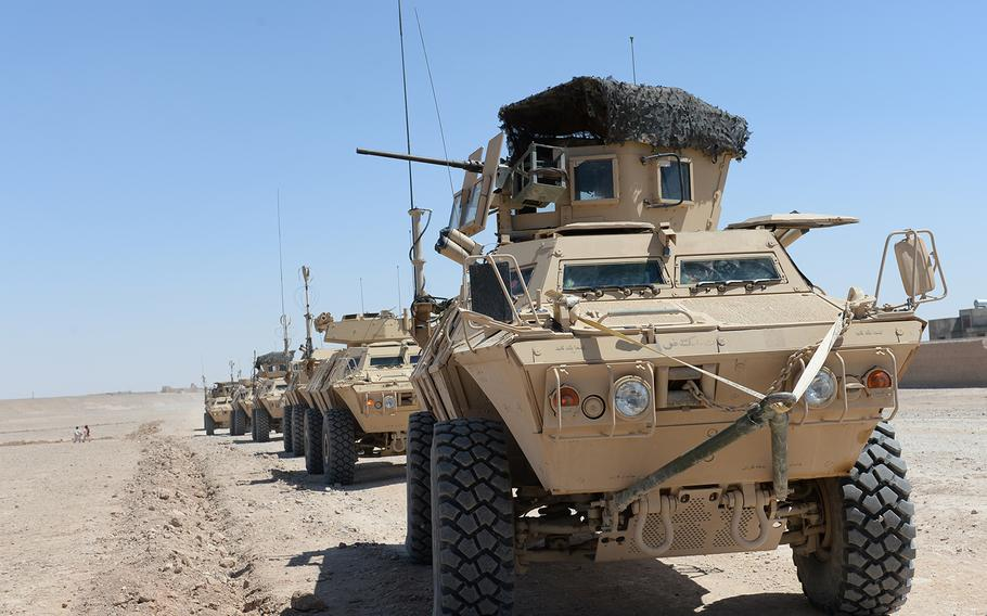 A row of armored personnel carriers sits idle outside the town of Gereshk in Helmand province during what turned out to be a faux Afghan army patrol, May 12, 2015. Officials said they lack the resources to continue the type of counterinsurgency patrols common during the coalition's presence in Helmand.
