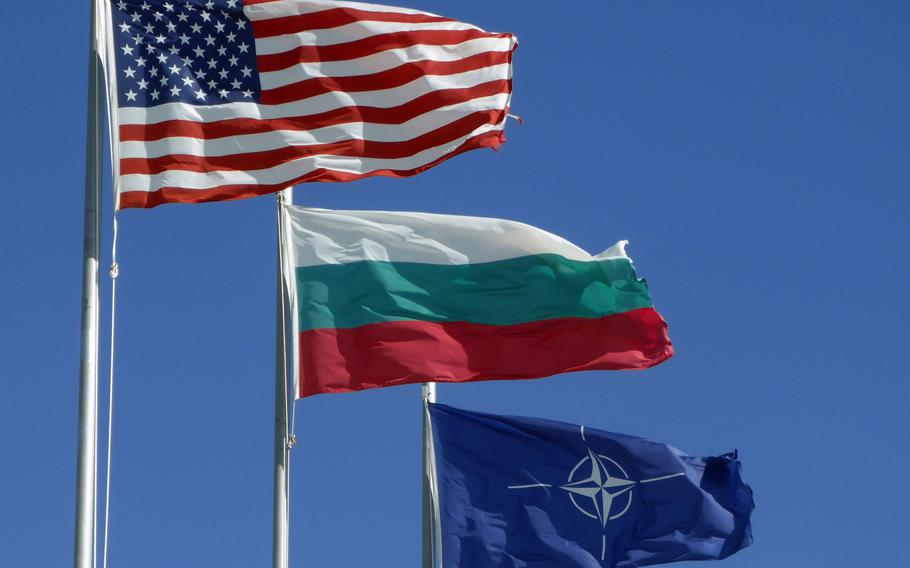 The American, Bulgarian and NATO flags fly over the American headquarters building at the Novo Selo Training Area, Bulgaria, June 26, 2015. The United States signed a defense cooperation agreement with Bulgaria in 2006 to use its military bases, two years after Bulgaria joined NATO.