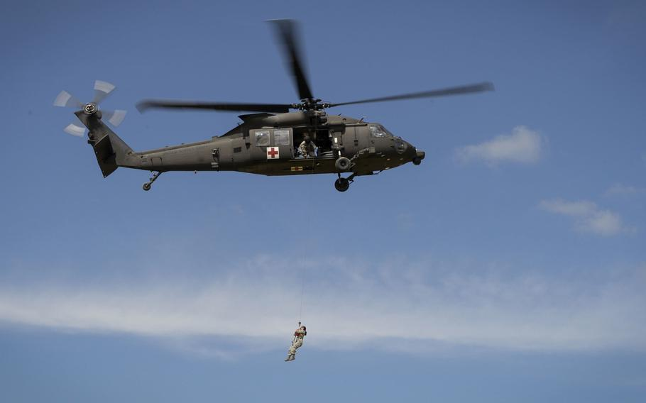 Airman 1st Class Natalie Powell, a 1st Combat Camera Squadron combat broadcaster, is hoisted up on a UH-60 Black Hawk medevac helicopter during a training evacuation at Fort McCoy, Wisc., on June 12, 2015.
