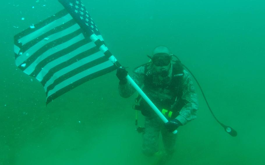 Tech. Sgt. Robert Barnes, 325th Communications Squadron quality assurance NCO in charge, holds the U.S.flag on June 26, 2015. Barnes had a re-enlistment ceremony 70 feet under water.